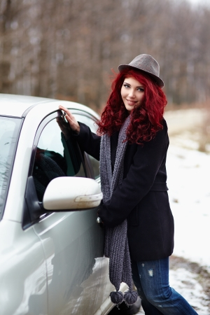 Cute readhead girl getting out of her car, outdoor portrait photo