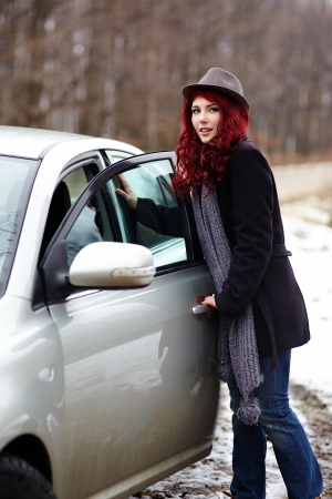 Cute readhead girl getting into her car, outdoor portrait photo