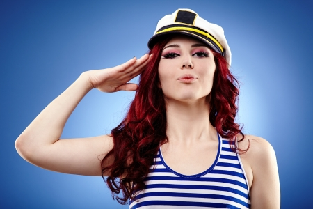 Young female sailor saluting, in glamour closeup, on blue background Stock Photo - 18822058