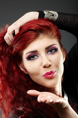 Closeup portrait of a beautiful redhead blowing kiss photo