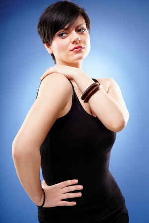 arms akimbo: Closeup portrait of a woman standing with hand on hip on blue background Stock Photo