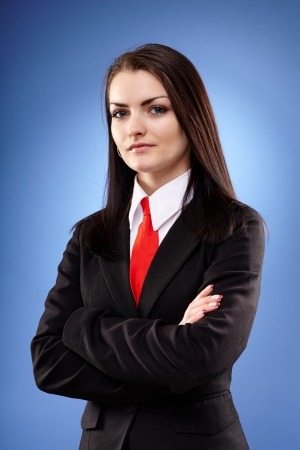 Closeup portrait of a businesswoman with crossed arms on blue background photo