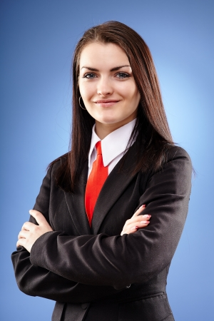 mujer con corbata: Primer retrato de una mujer de negocios con los brazos cruzados sobre fondo azul