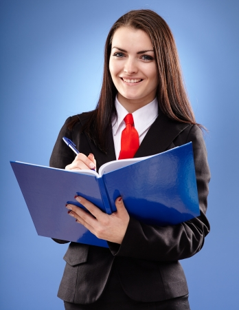 Young businesswoman holding a notebook in her hands in closeup pose, over blue background photo