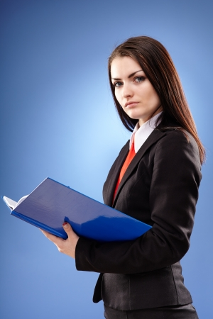 Young businesswoman in closeup pose holding a notebook in her hands, on blue background photo
