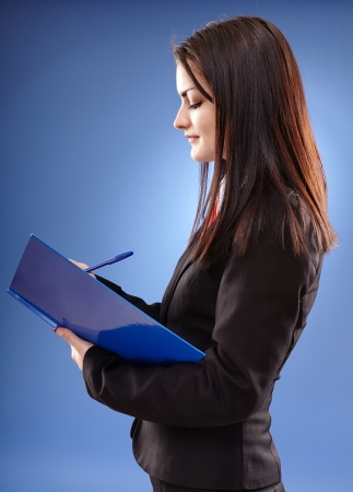 Profile closeup pose of a young businesswoman holding a notebook in her hands, on blue background photo