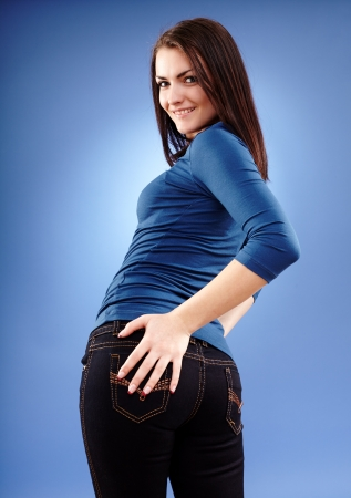 slap: Portrait of a woman standing with hand on her butt on blue background Stock Photo