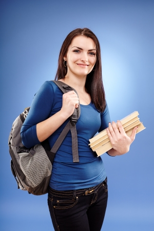 Portrait of a student girl with backpack and books on blue background photo