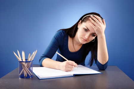 Closeup of an exhausted young student, having a migraine, sitting at her desk in closeup pose, on blue background