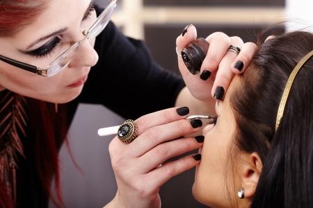 Closeup portrait of a woman having applied makeup by makeup artist 写真素材