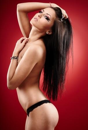Portrait d'une brune chaude coverig ses seins sur fond rouge