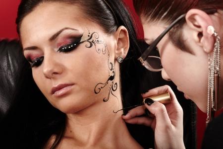 artist's model: Closeup of a brunette having applied face tattoo by makeup artist
