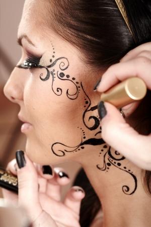 Gros plan d'une brune ayant appliqu? tatouage du visage de l'artiste de maquillage