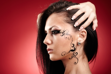 Closeup portrait of a beautiful brunette with facial tattoo photo