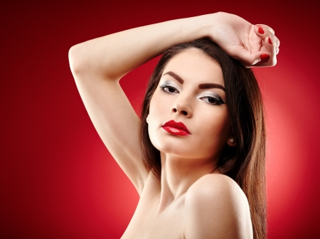 Closeup portrait of a beautiful glamour brunette on red background photo