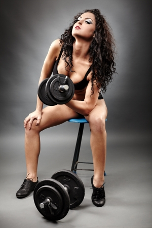 Full length portrait of a sexy woman lifting weights on gray background photo