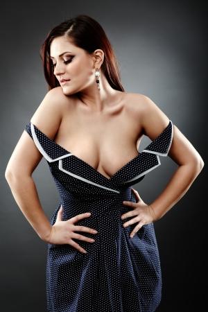 hot breast: Closeup позе большой грудью сексуальная женщина на сером фоне, взявшись за талию