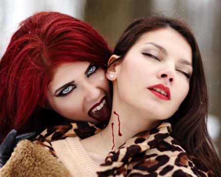 Zbliżenie rudowłosą wampir gryzie niewinną dziewczynę