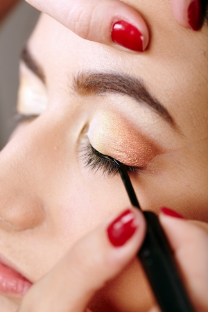 Closeup portrait of a beautiful woman having makeup applied Stock Photo