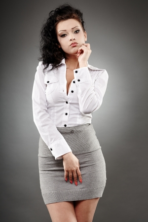 secretary skirt: Portrait of a beautiful businesswoman posing on gray background