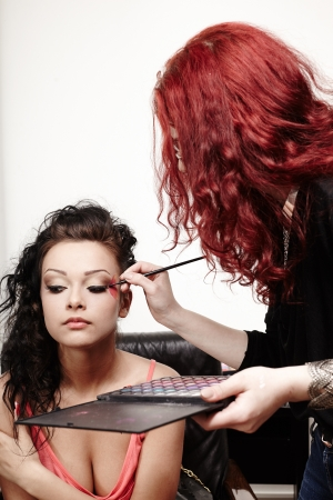 Portrait of a beautiful woman having makeup applied by makeup artist photo