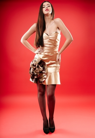 Full length portrait of a beautiful brunette posing on red background photo