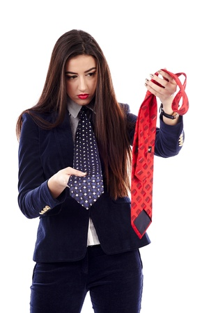 Portrait of a businesswoman choosing between blue and red necktie photo