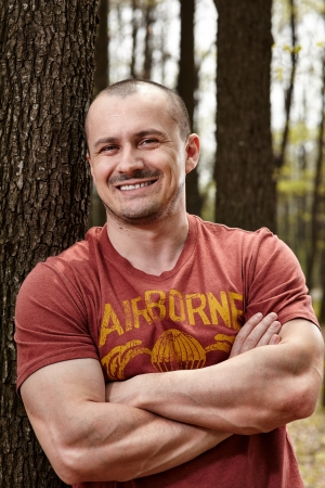 Closeup portrait of a handsome man leaning on a tree trunk Standard-Bild