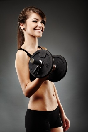 female muscle: Portrait of a beautiful woman lifting dumbbell Stock Photo