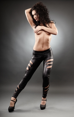 Full length portrait of a sexy brunette posing on gray background photo