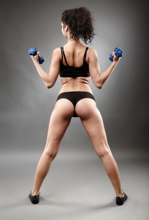 Full length portrait of a sporty woman lifting dumbbells photo