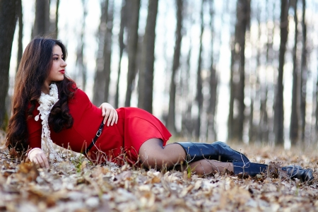 lying on leaves: Full length portrait of a beautiful woman laying in the woods Stock Photo