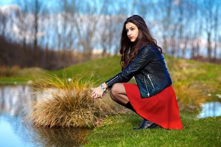 Portret piękna kobieta siedzi na brzegu jeziora w