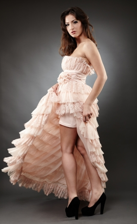 Full length portrait of a beautiful woman wearing ruffled dress on gray background photo