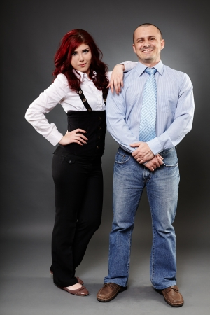 Full length portrait of two business partners posing on gray background photo