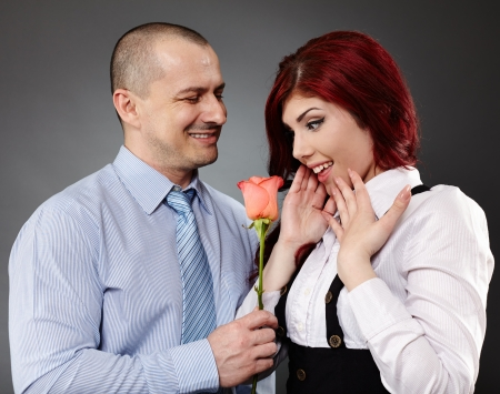 Portrait of a businessman giving a rose to his partner photo