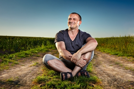 Portrait of a man sitting on a country road photo