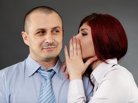 Secretary sharing some secrets to her boss, studio shot photo