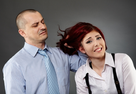 Angry boss acting violent on a female employee, while showing an expression of disgust on his face photo