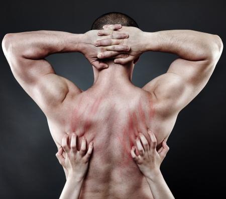 femme sexe: Les mains d'une femme plongeant ses ongles dans le dos de son partenaire musculaire