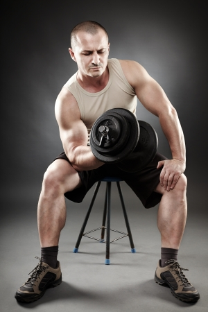 Man working with heavy dumbbells on gray background photo