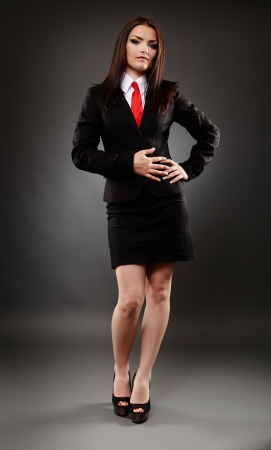 Full length of a young businesswoman on gray background photo