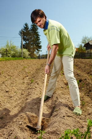 Young tiller working the land with a hoe in a sunny day photo