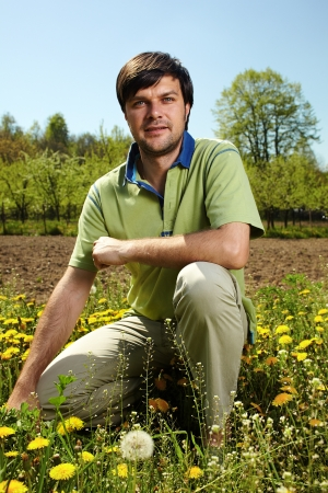 knelt: Young farmer knelt near his land in a sunny day