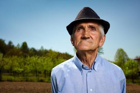 man field: Closeup portrait of a senior farmer outdoor