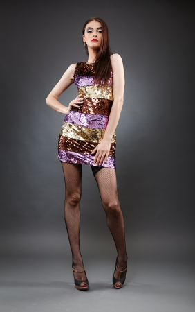 Full length of a young fashion model on gray background photo