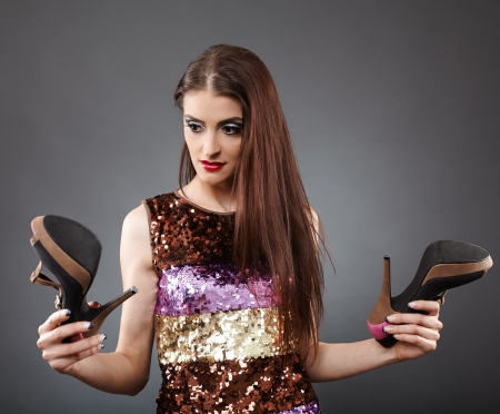 Young woman pondering whether or not to buy this pair of shoes Stock Photo - 20283272