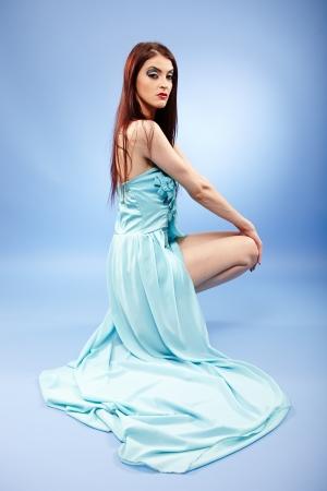 Beautiful redhead in blue dress full length portrait photo