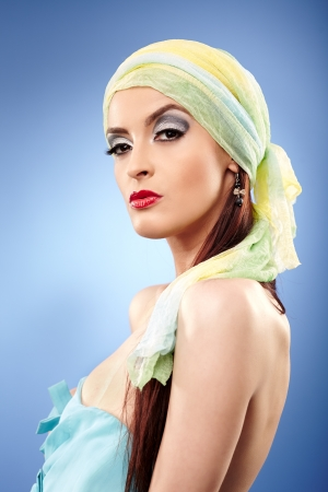Glamour closeup of a beautiful woman with head scarf on blue background photo
