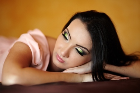 Closeup portrait of a young woman lying on the bed in her bedroom, with selective focus Stock Photo - 20245432